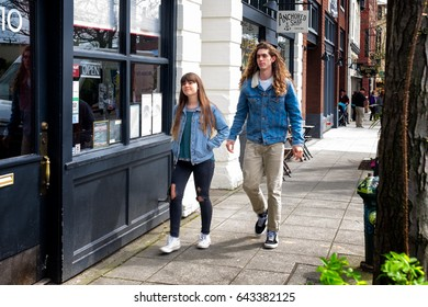 SEATTLE - April 8, 2017: Fashionable couple in trendy torn jeans and long hair walking down the sidewalk in Ballard, a neighborhood in Seattle with upscale restaurants, cafes, shops and galleries.