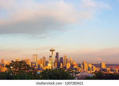 Seattle city landscape at sunset with Mount Rainier on horizon. City panorama and Mount Rainier snow top in clouds.