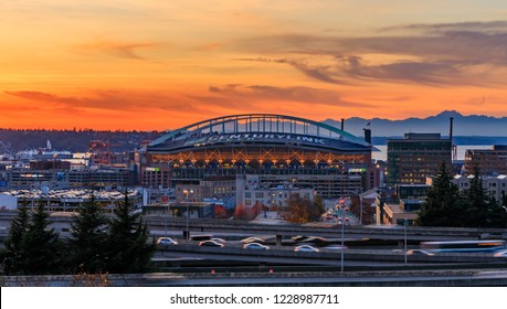 Seattle downtown and Safeco Field  beyond the I-5 I-90 freeway interchange at sunset in the fall with yellow foliage in the foreground view from Dr. Jose Rizal or 12th Avenue South Bridge
