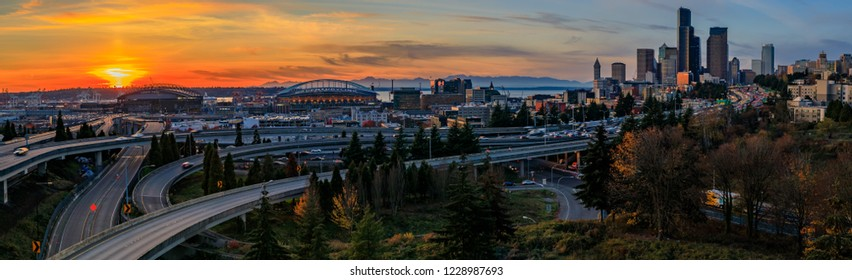Seattle downtown skyline and skyscrapers  beyond the I-5 I-90 freeway interchange at sunset in the fall with yellow foliage in the foreground view from Dr. Jose Rizal or 12th Avenue South Bridge