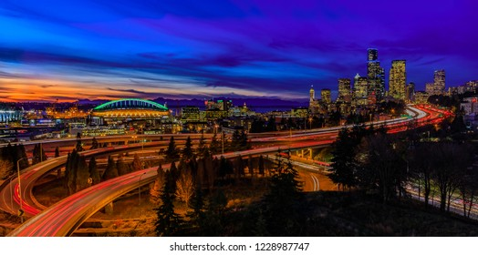 Seattle downtown skyline and skyscrapers  beyond the I-5 I-90 freeway interchange after sunset at blue hour with long exposure traffic trail lights from Dr. Jose Rizal or 12th Avenue South Bridge