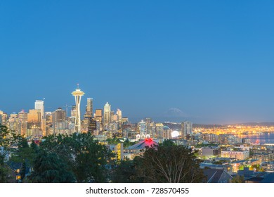 Seattle downtown skylines, urban office buildings with Mt Rainier at blue hour as seen from Kerry Park. Puget Sound is in the distance.