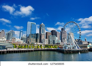 Seattle Ferris wheel, skyline and waterfront sunny day with blue sky and clouds.