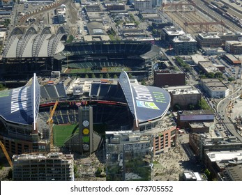 SEATTLE - JUNE 25: Aerial view of CenturyLink with people entering arena, train tracks, buildings, roads and Safeco Field in Seattle June 25, 2015. Home of Seattle Seahawks (NFL), Mariners (MLB).