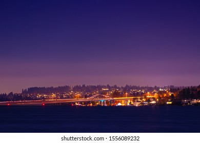 Seattle long exposure of city lights in the horizon over the water featuring a bridge with car trails at twilight.
