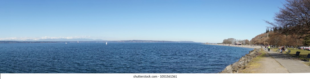 SEATTLE - MAR 11, 2018 -  Beachfront walkers with Sailboat on Puget Sound and Olympic mountains in background, Seattle, Washington