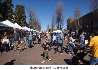 SEATTLE - MAR 11, 2018 - People explore the Ballard Farmer's Market on a spring day in Seattle, Washington