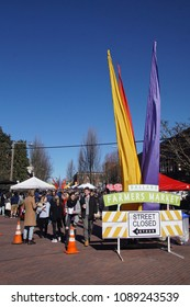 SEATTLE - MAR 11, 2018 - People explore the Ballard Farmer's Market on a spring day in Seattle, Washington