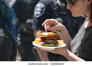 SEATTLE - MAY 18, 2019 - Eating fast food at  the 50th Annual University District Street Fair (oldest in the country),Seattle, Washington