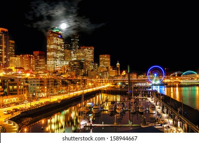 Seattle night view of the illuminated waterfront and skyline under a full moon breaking through clouds