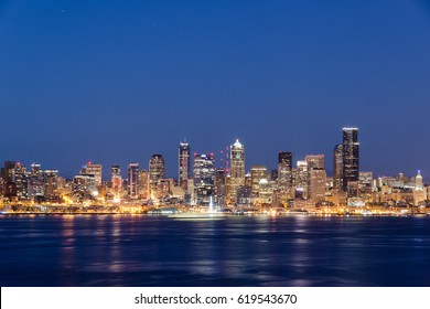 Seattle Skyline after Sunset, at Night, Reflecting on Water. Orange City Lights, Blue Sky.