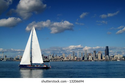 Seattle Skyline with a large sailboat in the foreground with the sails extending above the horizon. The Seattle Space Needle frames the left edge of the composition.
