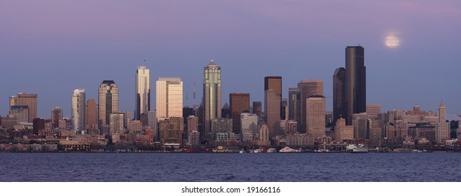 Seattle skyline and moon at sunset from Alki Beach