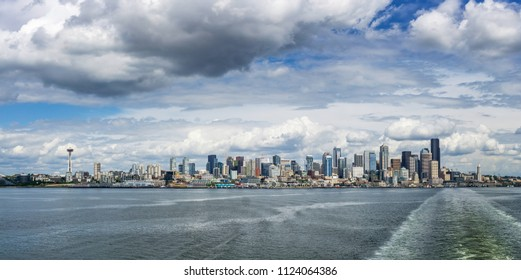 Seattle skyline seen from a Washington State ferry boat in the Puget Sound on a cloudy sunny day, WA, USA.