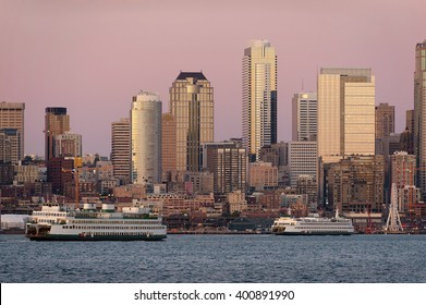 Seattle Skyline at Sunset. During a beautiful Seattle, Washington sunset ferry boats run between Bainbridge Island and downtown Seattle. Modern skyscrapers line the waterfront.