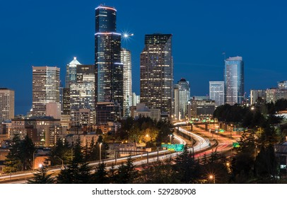 Seattle skyline and traffic light trails during blue hour.