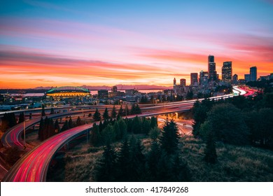 Seattle skylines and highway traffic motion under dramatic sunset.