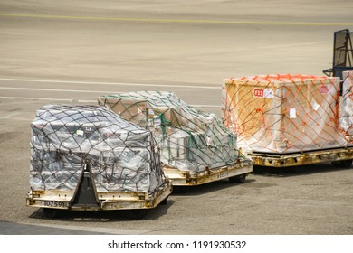 SEATTLE TACOMA AIRPORT, WA, USA - JUNE 2018: Air feight pallets wrapped in plastic and netting being towed across the apron at Seattle Tacoma airport.