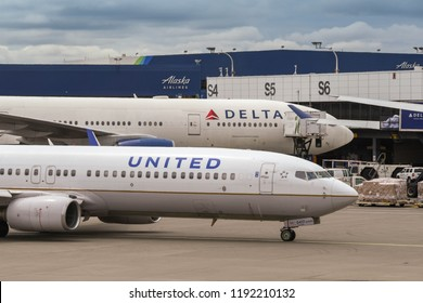 SEATTLE TACOMA AIRPORT, WA, USA - JUNE 2018: United Airlines Boeing 737 on departure taxiing past a Delita Airlines plane at Seattle Tacoma airport.