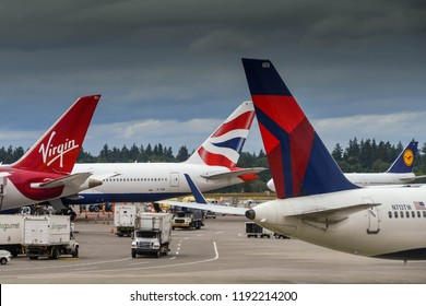 SEATTLE TACOMA AIRPORT, WA, USA - JUNE 2018: Tail fins of aircraft operated by British Airways, Virgin Atlantic and Delta Airlines at Seattle Tacoma airport.