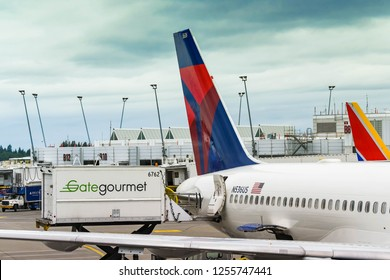 SEATTLE TACOMA AIRPORT, WA, USA - JUNE 2018: Gate Gourmet hydraulic lift truck loading food and other catering supplies onto a Delta Airlines Boeing 757 jet at Seattle Tacoma airport.