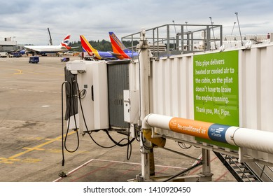 SEATTLE TACOMA AIRPORT, WA, USA - JUNE 2018: Jet bridge at Seattle Tacoma airport. An environmentally friendly notice explaining the pipe channels heated or cold air to a jet to save burning fuel