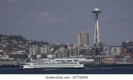SEATTLE, U.S.A. - JUNE 01, 2014: A Washington State Ferry crosses in front of the Space Needle in Elliot Bay.  Washington State Ferries operates the largest ferry system in the United States.