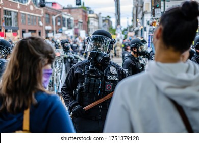 SEATTLE, USA - JUNE 6, 2020: Demonstrators watch Seattle Police setting a new perimeter after dispersing the crowd with flash bangs and pepper spray