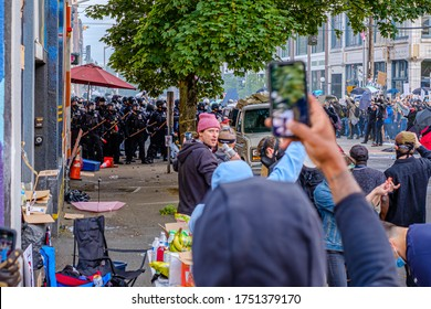SEATTLE, USA - JUNE 6, 2020: Seattle Police disperses demonstrators with flash bangs and pepper spray near a Seattle Police precinct