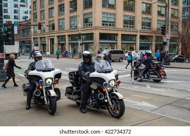 Seattle, USA March 04 2016 - Two police officers sitting on motorcycles on a city sidewalk prepare to leave after several officers questioned a man
