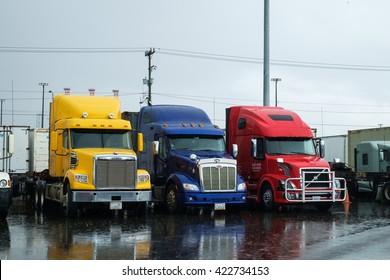 Seattle, USA March 06 2016 - Three semi trucks, without trailers, are parked in the rain waiting for their next load