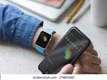 SEATTLE, USA - May 17, 2015: Man Using activity App on Apple Watch to See Calories Burned During Day. Comparing Watch and  iPhone Statistics.