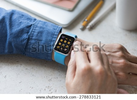 SEATTLE, USA - May 17, 2015: Man Wearing Sport Apple Watch with Blue Rubber Band. Emoji Collection Displayed.
