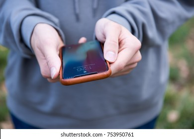 SEATTLE, USA - November 10, 2017: Hand Holding New iPhone X in Silver in Brown Leather Case