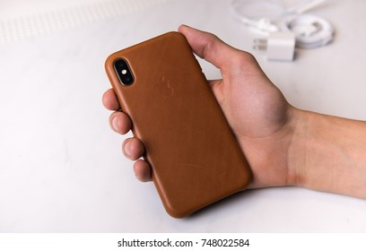 SEATTLE, USA - November 3, 2017: Hand Holding New iPhone X Silver in Brown Leather Protection Cover with Large Camera Opening.