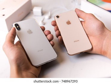 SEATTLE, USA - November 3, 2017: Hands Holding New iPhone X and iPhone 8. Glass Backs and Difference in Cameras Shown.