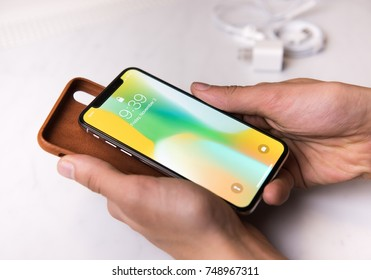 SEATTLE, USA - November 3, 2017: Hand Holding New iPhone X in Silver and Leather Protection Cover in Brown .