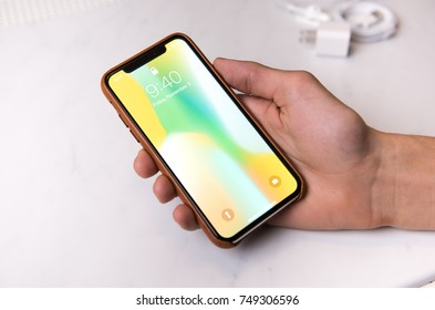 SEATTLE, USA - November 3, 2017: Hand Holding New iPhone X in Silver in Brown Leather Protection Cover.