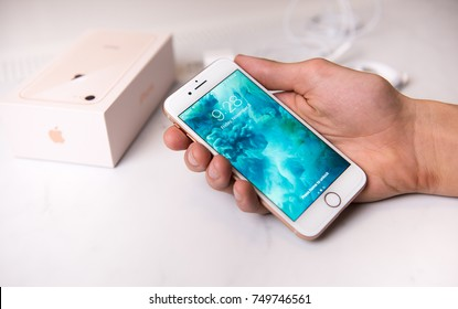 SEATTLE, USA - November 3, 2017: Hand Holding New iPhone 8 in Rose Gold Color. Blue and Green abstract Screen saver is Shown.