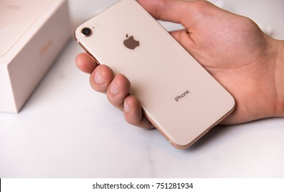 SEATTLE, USA - November 3, 2017: Hand Holding New iPhone 8 in Rose Gold Color. Glass Back Shown.