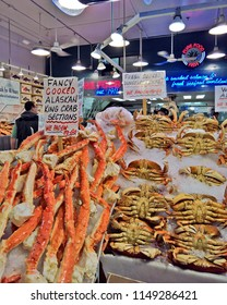 SEATTLE, WA - AUGUST 29, 2016: Freshly cooked Dungeness crab and Alaskan King crab legs on display at a store in Seattle`s public Pike Place Market. Customers wait in line to order.