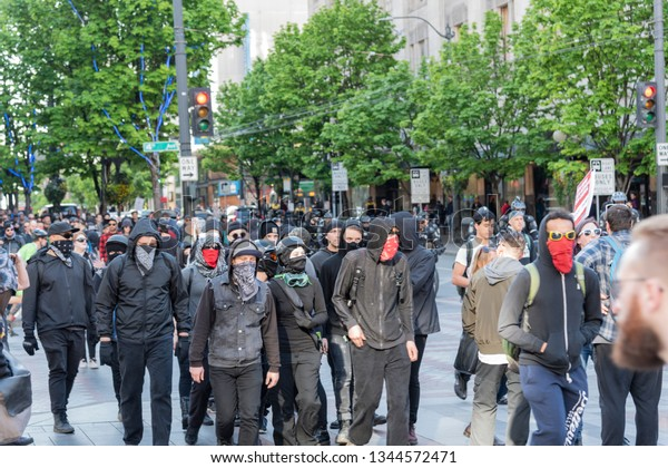 Seattle Wa circa May 2019 protester activists with dark clothing and covered faces marching in a large group downtown.
