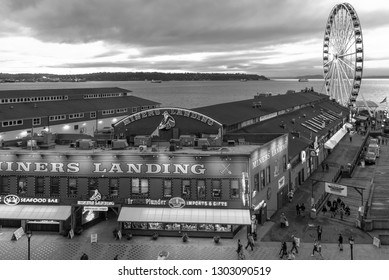 Seattle, Wa circa winter 2019 Miners Landing pier on the downtown waterfront with the Great wheel Ferris wheel at sunset, black and white.