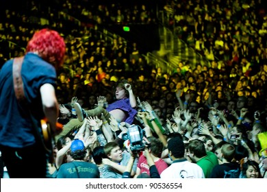 SEATTLE, WA -  DECEMBER 7: Cage the Elephant lead singer Matt Shultz crowd surfs over a sold out crowd at Key Arena in Seattle during the Deck the Hall Ball on December 7, 2011.
