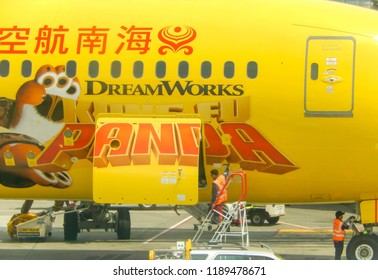 SEATTLE, WA - JUNE 2019: Airport worker closing the cargo hold door of a Hainan Airlines Boeing 787 Dreamliner at Seattle Tacoma airport.