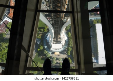 Seattle, WA - June 4, 2019: Rotating glass floor with two feet standing over 500 feet above the ground at the top of the Space Needle.