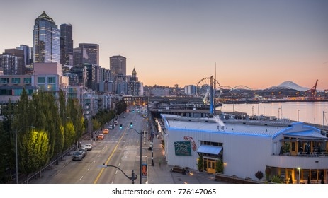 SEATTLE, WA - SEPTEMBER 1, 2017: High-rise buildings alongside Alaskan Way and Elliott Bay with ferry boats, cruise liners, sightseeing tour boats and a backdrop of Mount Rainier - Seattle, WA