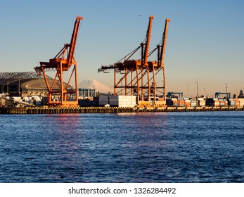 Seattle, WA, USA - April 1, 2016: Cargo cranes at the port of Seattle at sunset with Mount Rainier on the background