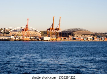Seattle, WA, USA - April 2, 2016: Port of Seattle at sunset with cargo cranes and CenturyLink field
