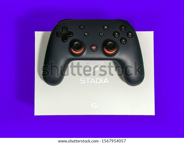 Seattle, WA / USA - circa November 2019: Closeup of a Google Stadia gaming controller resting on top of a white box against a colorful background